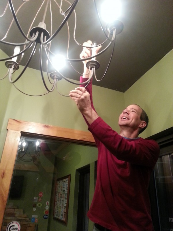 Bob Biribin, co-owner of The Wolf, installs new LED bulbs to save money on electric bills and conserve energy